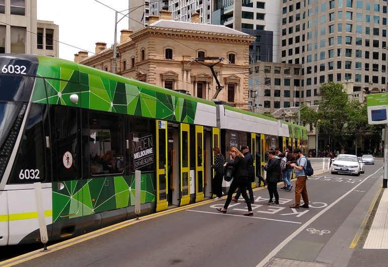A green bus on a city street