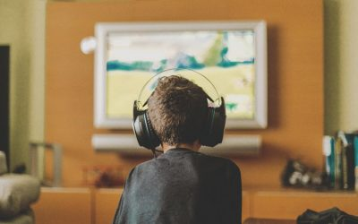 A kid wearing head phones and playing video games
